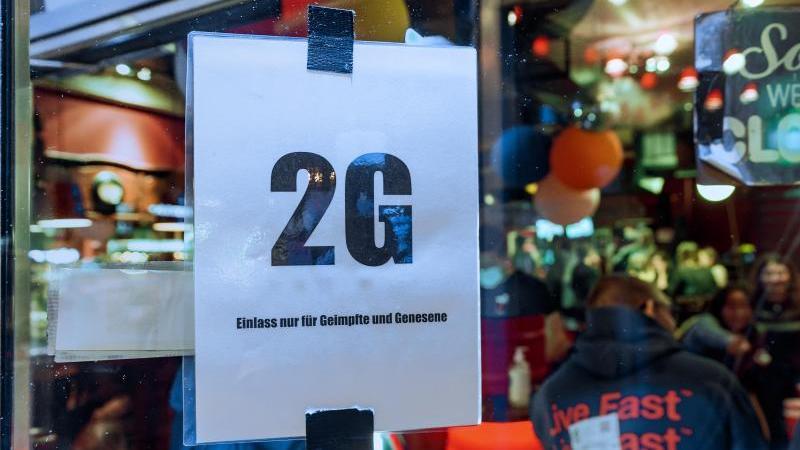 """Im Fenster einer Kneipe hängt ein Zettel mit dem Text """"2G, Einlass nur für Geimpfte und Genesene"""". Foto: Markus Scholz/dpa/Symbolbild"""