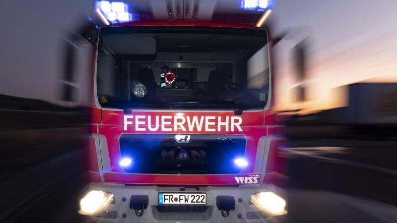 Ein Feuerwehrfahrzeug steht mit eingeschaltetem Blaulicht auf einer Straße. Foto: Patrick Seeger/dpa/Symbolbild