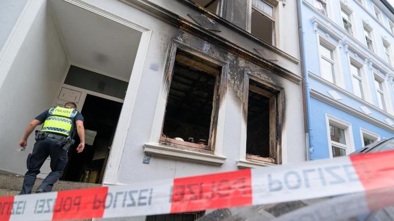 Ein Polizist betritt den Hauseingang neben der Brandwohnung.