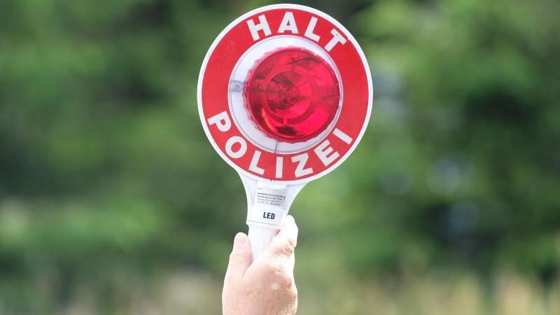 Eine Polizistin hält während einer Polizeikontrolle eine rote Winkerkelle in die Höhe. Foto: Sebastian Willnow/zb/dpa/Symbolbild