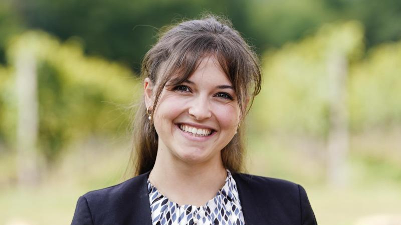 Sina Erdrich (Baden), Kandidatin bei der Wahl zur Deutschen Weinkönigin, steht vor einem Weinberg. Foto: Uwe Anspach/dpa