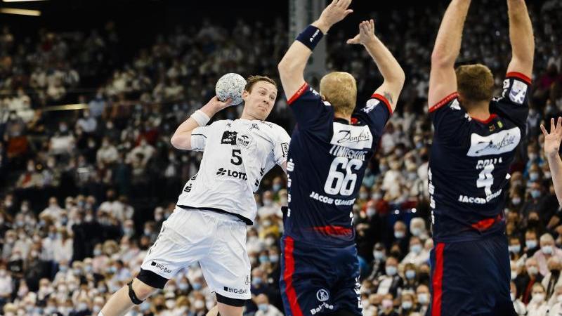 Flensburgs Anton Lindskog (M) und Johannes Golla (r) versuchen Kiels Sander Sagosen zu blocken. Foto: Frank Molter/dpa