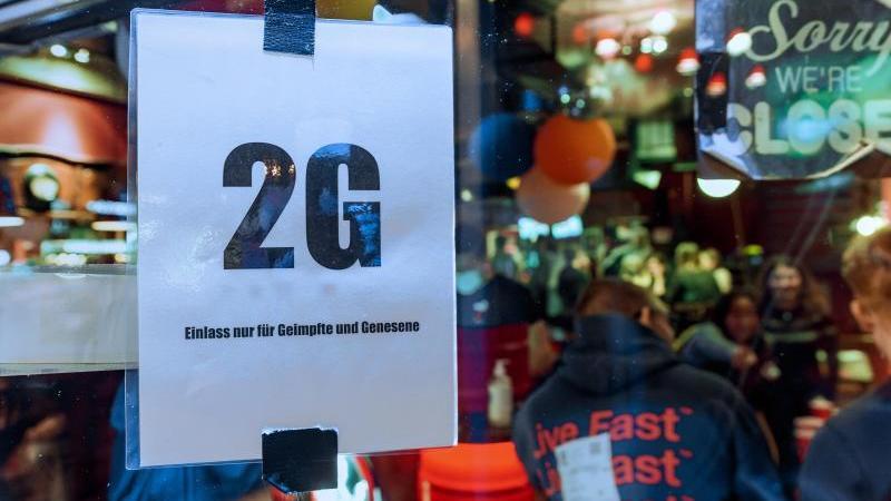 """Im Fenster einer Kiez-Kneipe hängt ein Zettel mit Text """"2G, Einlass nur für Geimpfte und Genesene"""". Foto: Markus Scholz/dpa/Archivbild"""
