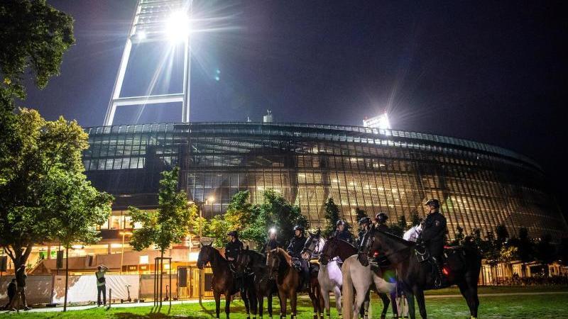 Die berittene Polizei steht mit ihren Pferden vor dem Weserstadion. Foto: Sina Schuldt/dpa