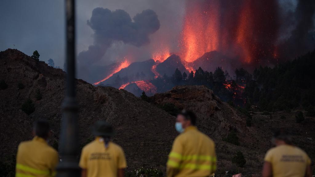 19.09.2021, Spanien, La Palma: Feuerwehrmänner beobachten den Vulkan Cumbre Vieja auf der kanarischen Insel La Palma. Der Ausbruch hatte sich in den vergangenen Tagen durch Tausende kleine Erdbeben und eine leichte Anhebung des Erdbodens angekündigt.