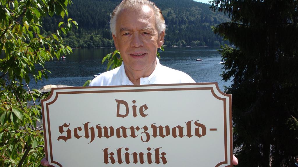 """Schauspieler Klausjürgen Wussow hält vor der Kulisse des Titisees im Schwarzwald ein Schild mit der Aufschrift """"Die Schwarzwaldklinik"""" in den Händen"""