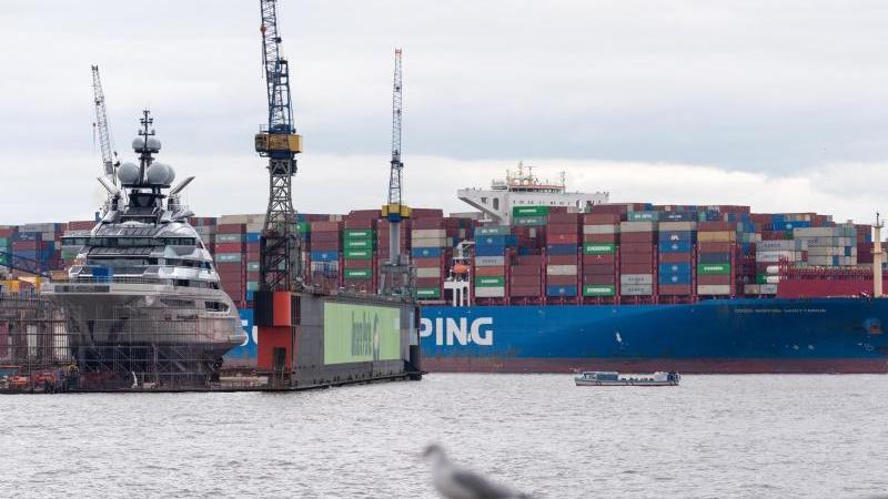 """Eine Yacht liegt im Dock 11 während das Containerschiff """"Cosco Shipping Sagittarius"""" manövriert. Foto: Jonas Walzberg/dpa"""
