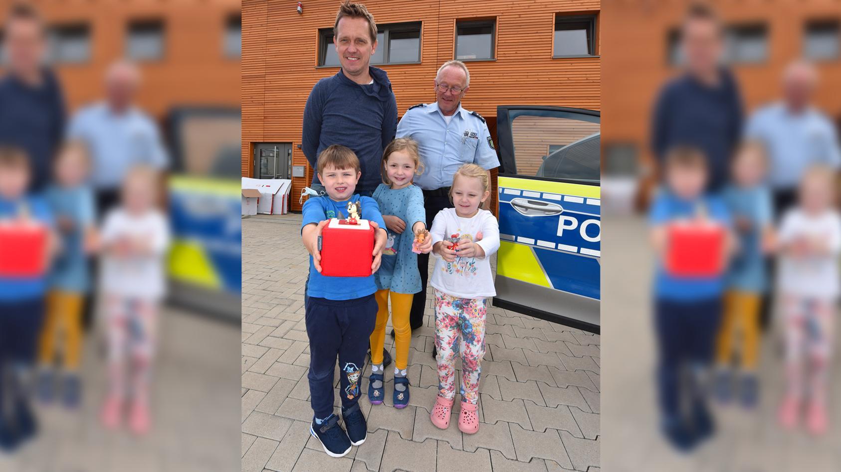 """Polizeihauptkommissar Rainer Stach übergab die rote """"Tonie""""-Hörspielbox und drei Figuren an den stellvertretenden Leiter der Kita """"Wundertüte"""", Marcel Rau, und drei Kinder."""