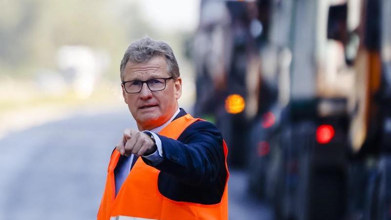 Verkehrsminister Bernd Buchholz steht vor Baufahrzeugen auf der A215. Foto: Frank Molter/dpa/Archiv