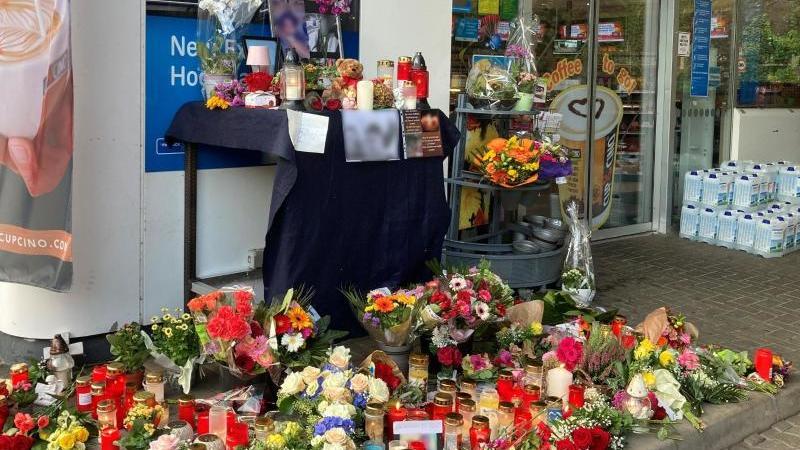 Blumen und Kerzen sind vor einer Tankstelle aufgestellt. Foto: Birgit Reichert/dpa/archivbild