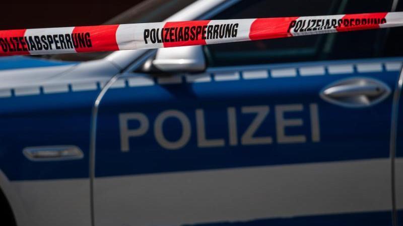 Ein Polizeiauto steht hinter einem Absperrband der Polizei. Foto: Robert Michael/dpa-Zentralbild/dpa/Symbolbild