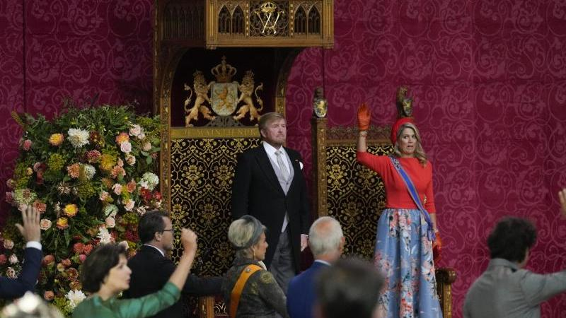 Maxima, Königin der Niederlande, und Mitglieder des Parlaments stehen für einen dreifachen Salut vor Willem-Alexander, König der Niederlande. Foto: Peter Dejong/AP/dpa