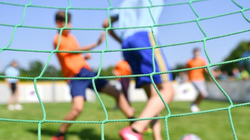 Kinder spielen auf einem Sportplatz Fußball. Foto: Uwe Anspach/dpa/Symbolbild