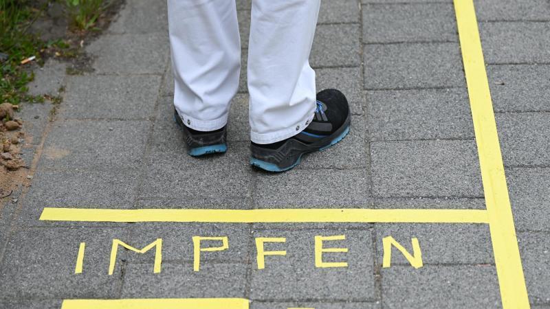 """Ein Mann steht an einem Covid-19-Impfcenter hinter der Bodenaufschrift """"Impfen"""". Foto: Arne Dedert/dpa/POOL/dpa/Symbolbild"""