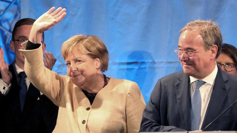Angela Merkel (CDU), Bundeskanzlerin, und Armin Laschet (CDU), Unions-Kanzlerkandidat, stehen bei einem gemeinsamen Wahlkampfauftritt in Stralsund auf der Bühne. Foto: Bernd Wüstneck/dpa-Zentralbild/dpa