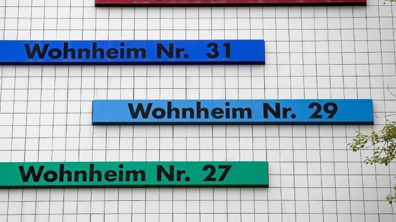 Verschiedenfarbige Schilder weisen den Weg zu den Eingängen in einem Studentenwohnheim. Foto: Hendrik Schmidt/dpa-Zentralbild/dpa
