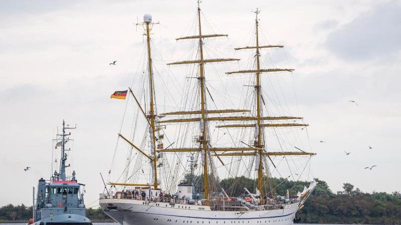 """Die """"Gorch Fock"""" fährt, von einem Schlepper begleitet, aus dem Hafen. Foto: Sina Schuldt/dpa/Archivbild"""