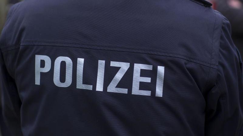 """""""Polizei"""" steht auf der Uniform eines Polizisten. Foto: Jens Büttner/zb/dpa/Symbolbild"""