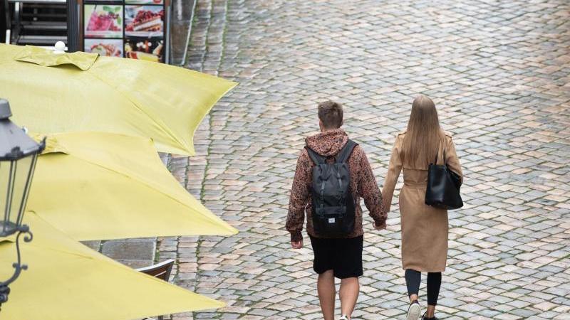 Passanten gehen an Restaurants auf der Münzgasse entlang. Foto: Sebastian Kahnert/dpa-Zentralbild/dpa/Archivbild