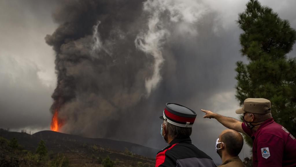 23.09.2021, Spanien, La Palma: Polizeibeamte und Gemeindearbeiter beobachten, wie die Lava während eines Vulkanausbruchs fließt. Der Vulkan in der Cumbre Vieja im Süden der Kanareninsel, der am 19. September 2021 erstmals seit 50 Jahren wieder ausgeb