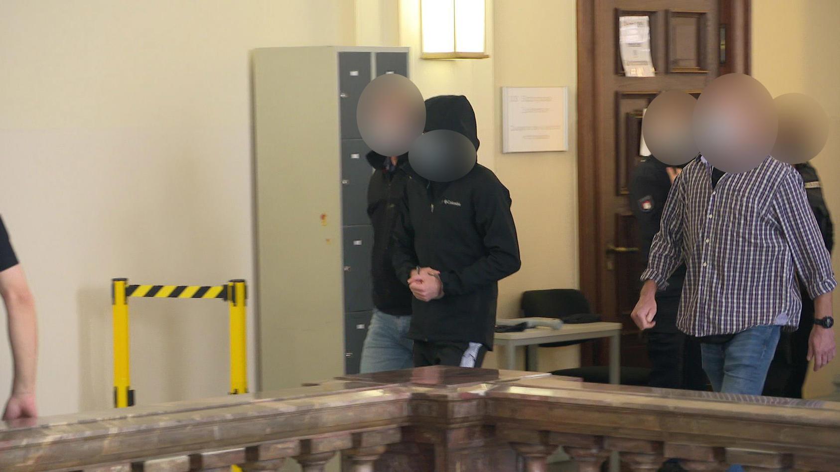 Einer der Angeklagten wird in den Gerichtssaal geführt.