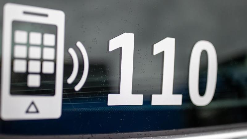 Die Nummer des Polizeinotrufs 110 steht auf der Scheibe eines Polizeifahrzeugs. Foto: Daniel Karmann/dpa/Symbolbild