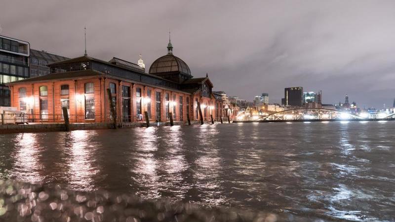 Blick auf die Fischauktionshalle am Fischmarkt während eines nächtlichen Hochwassers. Foto: Jonas Walzberg/dpa