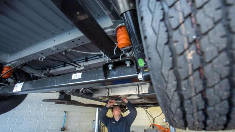 Ein Mechaniker montiert Batterieblöcke in einer Autowerkstatt. Foto: Jens Büttner/dpa-Zentralbild/dpa
