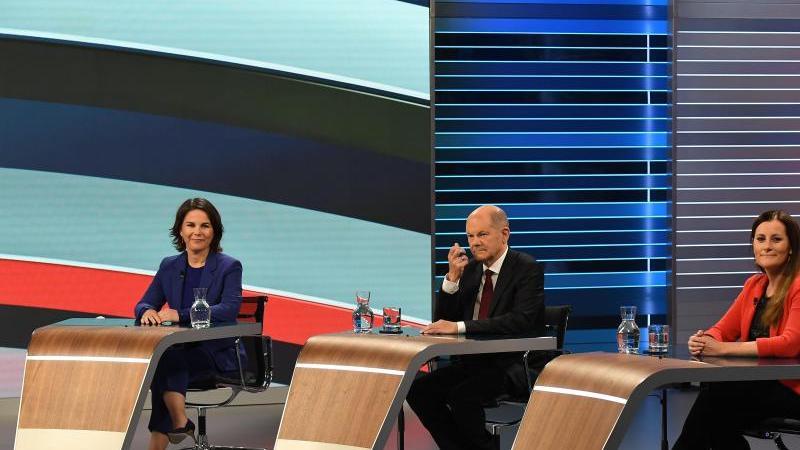 """Annalena Baerbock (l.), Olaf Scholz und Janine Wissler sitzen bei der TV-Debatte """"Wahl 2021 Schlussrunde"""". Foto: Tobias Schwarz/POOL/dpa"""