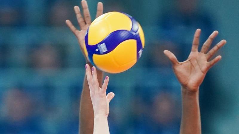 Spieler strecken ihre Arme in Richtung eines Volleyballs. Foto: Uwe Anspach/dpa/Symbolbild