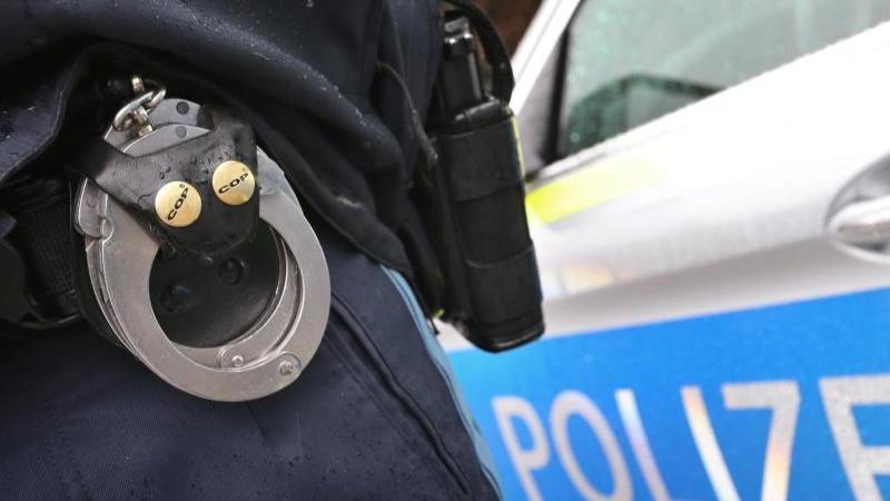 Ein Polizist mit Handschellen und einer Pistole am Gürtel steht vor einem Streifenwagen. Foto: Karl-Josef Hildenbrand/dpa