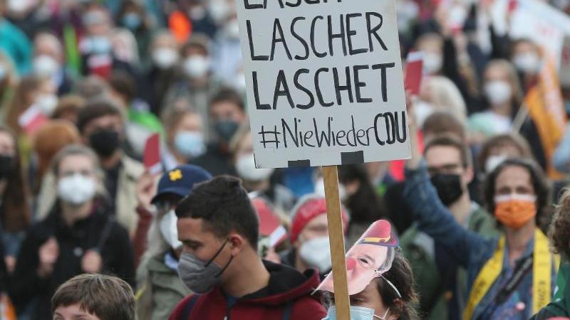 EinDemonstrant hält ein Plakat hoch. Foto: David Young/dpa/Symbolbild