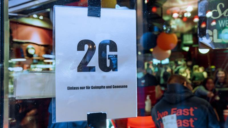 """Im Fenster einer Kneipe hängt ein Zettel mit dem Text """"2G, Einlass nur für Geimpfte und Genesene"""". Foto: Markus Scholz/dpa/Archivbild"""
