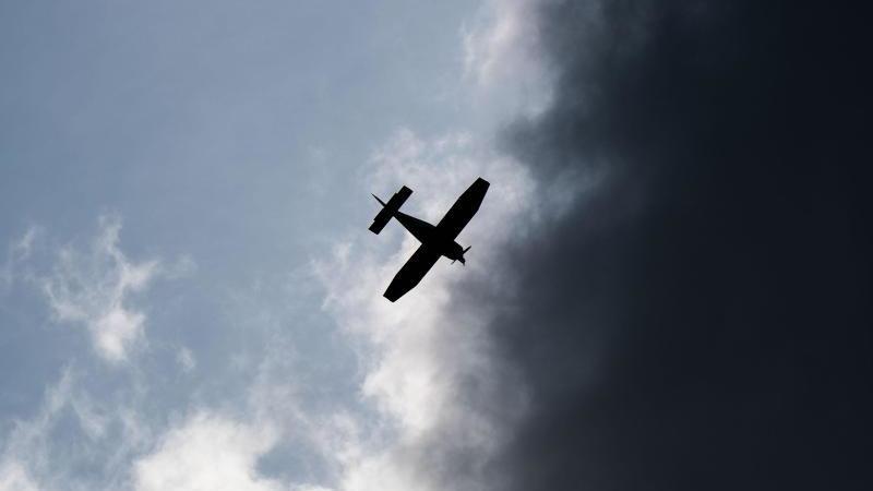 Ein Kleinflugzeug fliegt vor dunklen Wolken. Foto: Julian Stratenschulte/dpa/Archivbild