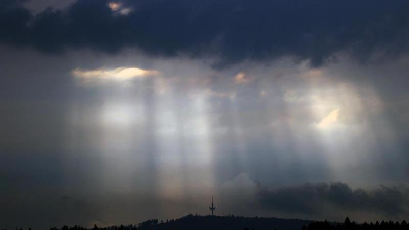 Sonnenstrahlen dringen durch Wolkenlücken. Foto: Karl-Josef Hildenbrand/dpa/Archivbild