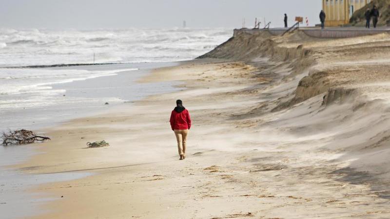 Ein Mann spaziert über den Strand unterhalb der Abbruchkante der letzten Sturmflut. Foto: Peter Kuchenbuch-Hanken/dpa/Archivbild