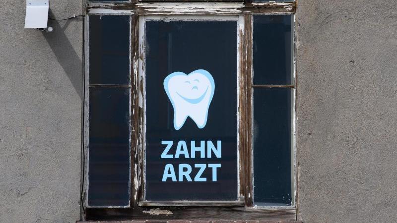 Zahnarzt steht an einem Fenster eines Hauses, in dem sich eine Zahnarztpraxis befindet. Foto: Robert Michael/dpa-Zentralbild/dpa/Archivbild