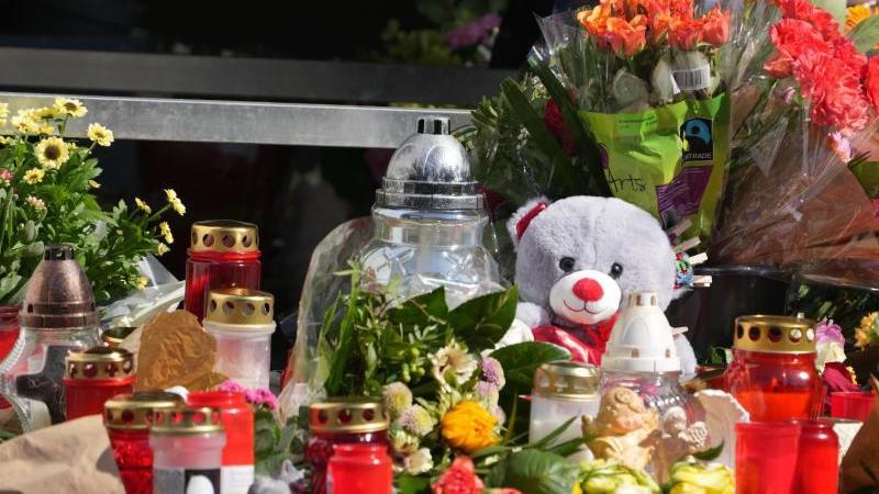 Blumen, Kerzen und Botschaften an das Opfer liegen an einer Tankstelle in der Innenstadt. Foto: Thomas Frey/dpa