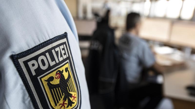 Ein Polizist steht in einer Leitstelle. Foto: Boris Roessler/dpa/Symbolbild
