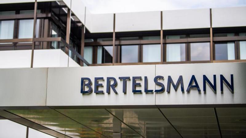 Ein Schild mit dem Logo von Bertelsmann steht vor der Zentrale. Foto: Lino Mirgeler/dpa/Archivbild