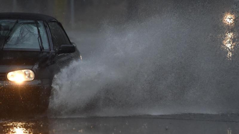 Ein Auto fährt durch eine tiefe Pfütze die sich durch Starkregen auf einer Straße gebildet hat. Foto: Caroline Seidel/dpa/Archivbild