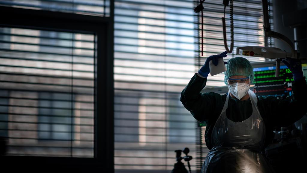 dpatopbilder - 23.09.2021, Nordrhein-Westfalen, Essen: Josephin Kampmann, Gesundheits- und Krankenpflegerin, steht in einem Zimmer der Corona-Intensivstation des Universitätsklinikums Essen und behandelt einen Patienten. Patienten mit Corona-Infektio