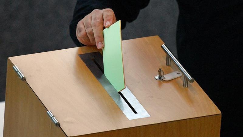 Ein Stimmzettel wird in eine Wahlurne geworfen. Foto: Martin Schutt/dpa-Zentralbild/dpa/Symbolbild