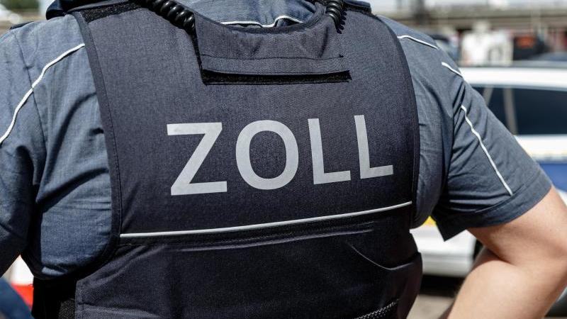 """Ein Beamter trägt während seines Dienstes eine Schutzweste mit der Rückenaufschrift """"Zoll"""". Foto: Markus Scholz/dpa/Symbolbild"""