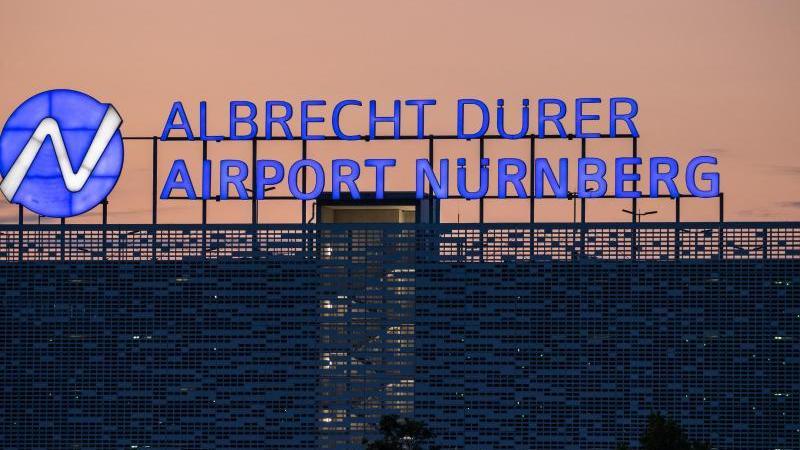 Die Sonne geht hinter einem Parkhaus am Albrecht-Dürer-Airport Nürnberg unter. Foto: Daniel Karmann/dpa/Archivbild