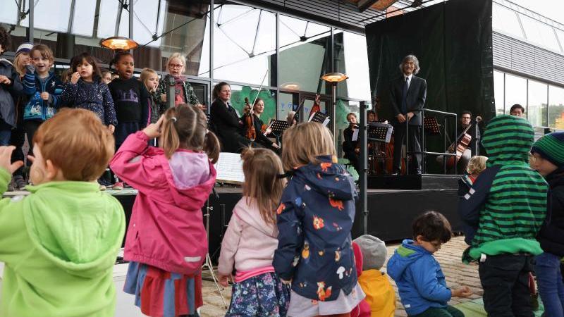 Kent Nagano (r) verfolgt den Gesang eines Kinderchors bei den Feierlichkeiten. Foto: Christian Charisius/dpa