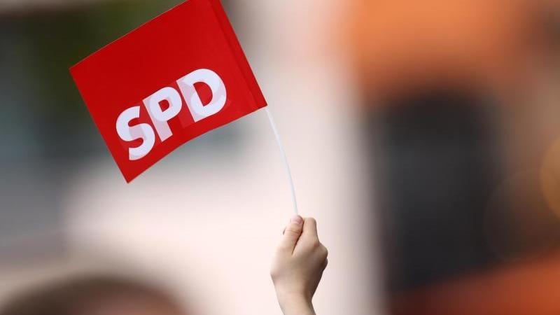 Ein Unterstützer schwenkt bei einer Wahlkampfveranstaltung ein SPD-Fähnchen. Foto: Rolf Vennenbernd/dpa