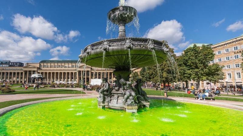 Grünes Wasser sprudelt aus einem Brunnen am Schlossplatz. Foto: Christoph Schmidt/dpa