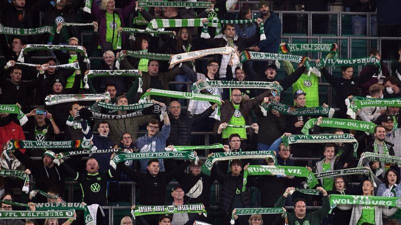 Fans vom VfL Wolfsburg stehen mit Schals auf der Tribüne. Foto: Swen Pförtner/dpa/Archivbild