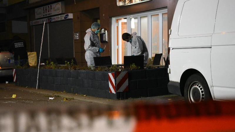 Ermittler arbeiten vor der Gaststätte in Mannheim, in der mehrere Menschen durch Schüsse verletzt worden sind.